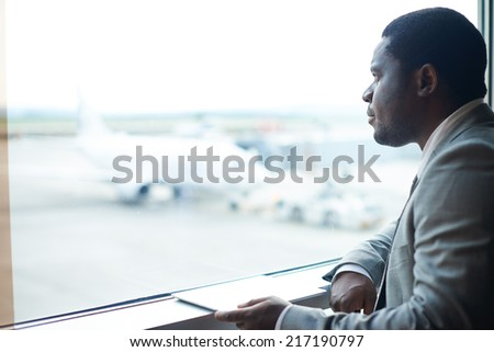 Serious businessman with digital tablet looking through window in airport - stock photo