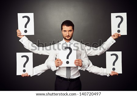 serious businessman with five hands holding placards with question marks - stock photo