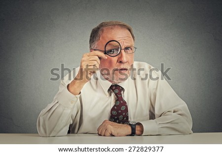 Serious businessman with glasses skeptically looking at you sitting at his office desk isolated on gray wall background. Human face expression, body language, attitude, perception  - stock photo