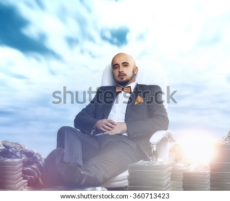 Serious businessman with lots of money around. Business concept - stock photo