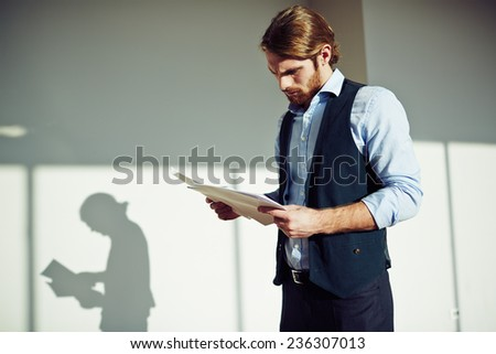 Serious businessman working with papers - stock photo