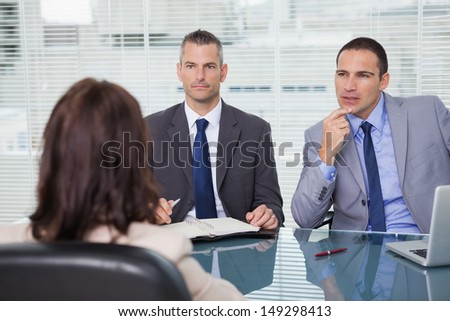 Serious businessmen having an interview in bright office - stock photo