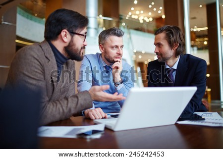 Serious businessmen in smart casual discussing data - stock photo