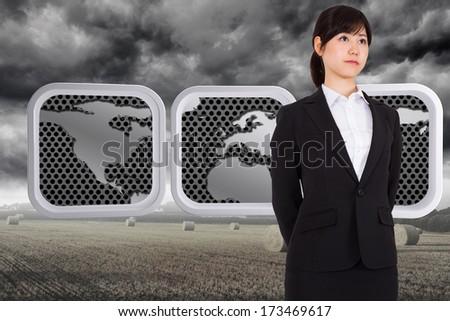 Serious businesswoman against misty landscape with bales of straw - stock photo