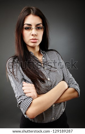 Serious businesswoman holding her arms crossed in closeup pose on gray background - stock photo