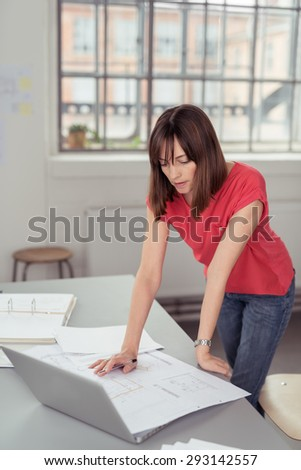Serious Businesswoman Leaning Against the Worktable with Laptop Computer While Reading Some Documents - stock photo