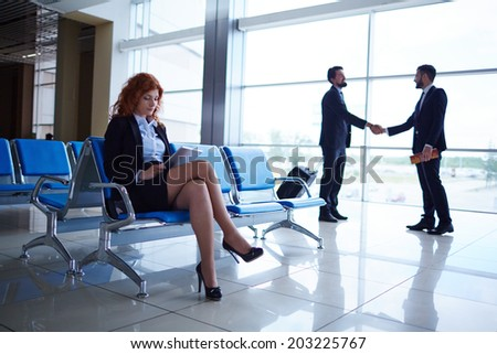 Serious businesswoman sitting in airport on background of her colleagues handshaking by the window - stock photo