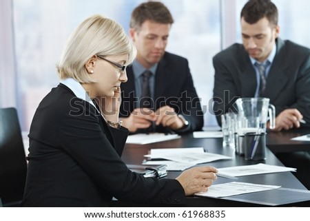 Serious businesswoman talking on phone at meeting with businessmen in background.? - stock photo
