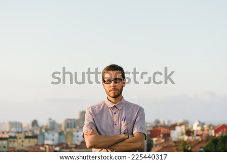 Serious casual man with smart geek looking standing against city background crossing arms. - stock photo