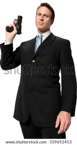 Serious Caucasian man with short black hair in business formal outfit holding handgun - Isolated - stock photo