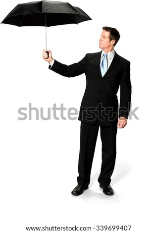 Serious Caucasian man with short black hair in business formal outfit using umbrella - Isolated - stock photo