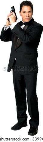 Serious Caucasian man with short black hair in evening outfit holding handgun - Isolated - stock photo