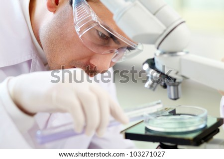 Serious clinician studying chemical element in laboratory - stock photo
