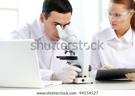 Serious clinicians analyzing chemical elements in laboratory - stock photo