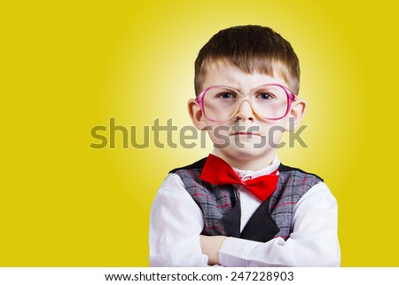Serious Confident little boy nerd isolated over yellow background. - stock photo