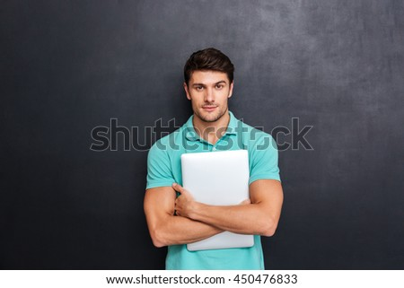 Serious confident young man standing and holding laptop over blackboard background - stock photo