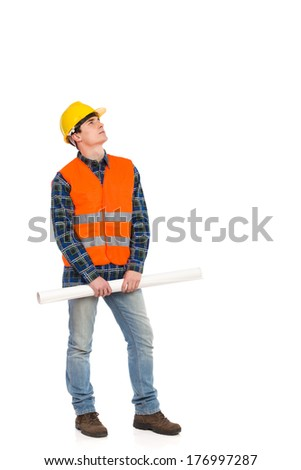 Serious construction worker in yellow helmet and orange waistcoat holding rolled paper plan and looking up. Full length studio shot isolated on white. - stock photo