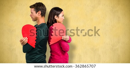 Serious couple standing back to back against orange background - stock photo