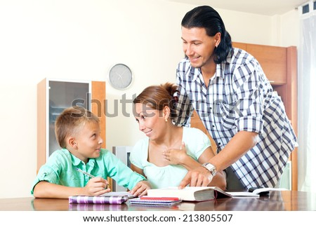 Serious couple with clever schoolboy  doing homework in a home   - stock photo