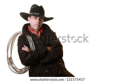 Serious cowboy leaning back on chair with red scarf, duster, black hat, and rope on shoulder, isolated on white - stock photo