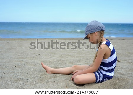 Serious cute little girl sitting on the beach - stock photo