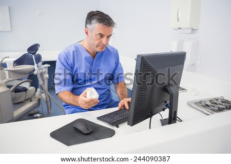Serious dentist using computer and holding model in dental clinic - stock photo