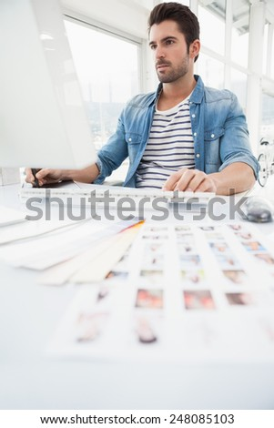 Serious designer using digitizer and computer in the office - stock photo
