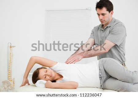 Serious doctor using his fingertips on a patient in a bright room - stock photo