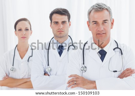Serious doctors posing together in bright office - stock photo