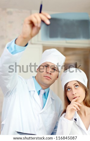 serious  doctors stares x-ray scan  in clinic - stock photo