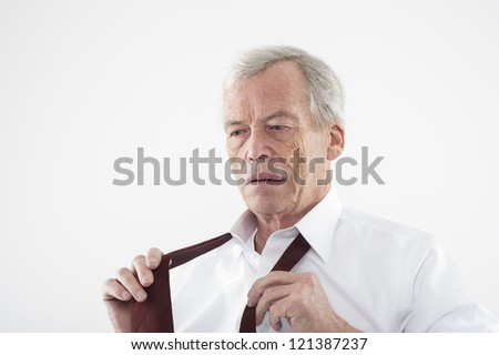 Serious elderly man with a pensive expression putting on his tie holding the two ends in his hands as he stands thinking, head and shoulders studio portrait - stock photo