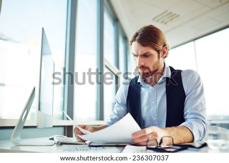 Serious employee working with papers in office - stock photo