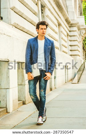 Serious European college student studying in New York. Wearing blue blazer, jeans, sneakers, hands holding a laptop computer, a young guy walking on campus, thinking. Casual Fashion. Instagram effect. - stock photo