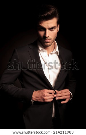 serious fashion business man opening his coat and looks to the camera - stock photo