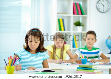 Serious girl drawing at workplace with schoolmates on background - stock photo