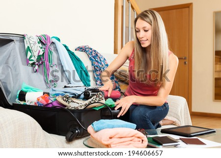 Serious girl trying to find room for all the things in trunk - stock photo