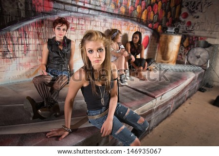 Serious group of female teenagers sitting by wall - stock photo