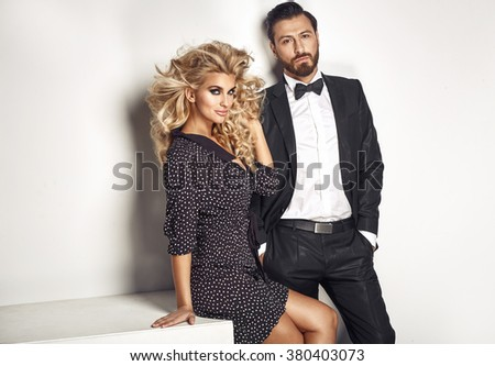 Serious handsome guy with his blond lovely wife - stock photo