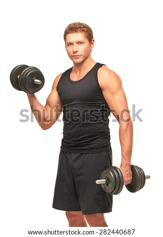 Serious handsome powerful young sportsman pumping up bicep muscles with black dumbbells, looking at camera. Dressed in black shirt and shorts. Isolated on white background - stock photo