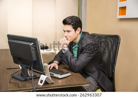 Serious handsome young businessman sitting at his desk in the office working at computer - stock photo