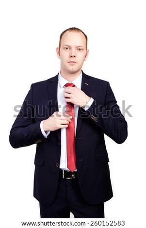 Serious head of the firm in a business suit corrects red tie on an isolated white background. - stock photo