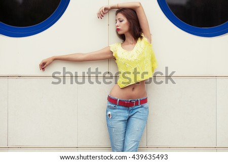 Serious hipster girl dancing in blue jeans in the summer city. Modern youth lifestyle concept. Copy-space. Outdoor shot - stock photo