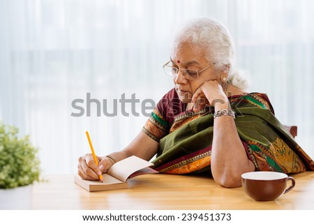 Serious Indian woman writing or sketching something in the notebook - stock photo