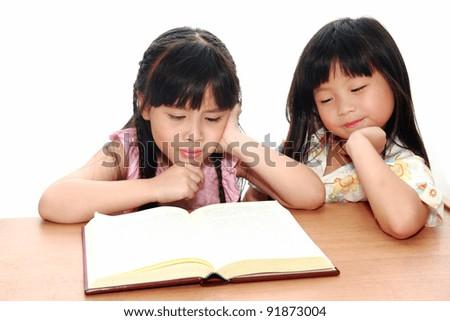 serious little asian girl  reading a book - stock photo