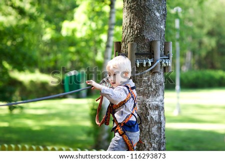 serious little boy climbing at a canopy tour - stock photo