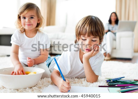 Serious little boy drawing and his sister eating chips lying on the floor - stock photo