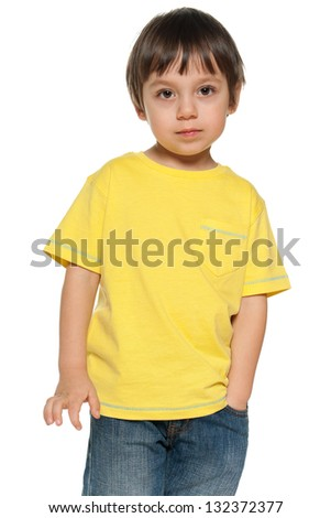 Serious little boy in yellow shirt on the white background - stock photo