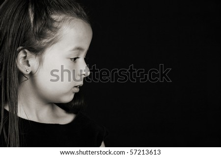 Serious little brunette girl against a black background - stock photo