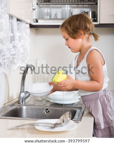 Serious little child washing dishes at domestic kitchen - stock photo