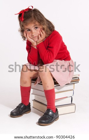Serious little girl sitting on a pile of books - stock photo